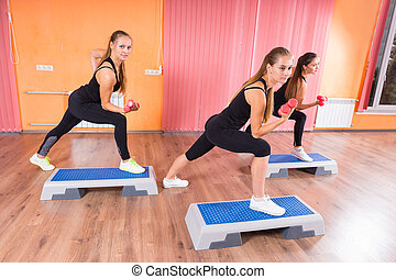 Girls Lifting Weights While Stepping on Platforms - Three...