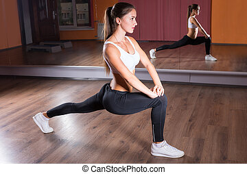 Young Woman Stretching in Lunge Position in Studio - Full...