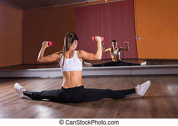 Woman Doing Splits and Lifting Weights in Studio