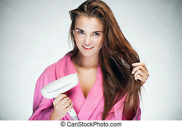 Fresh girl drying her long hair with blow dryer - Healthy...
