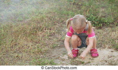 Little girl in sandbox - Girl is played in sandbox of...
