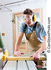 Carpenter using electric saw in carpentry
