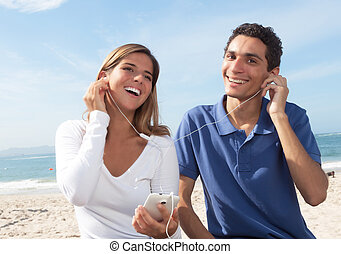 Young couple listening to music from the phone with beach,...