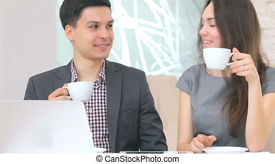 Young attractive business man and woman drink coffee and...
