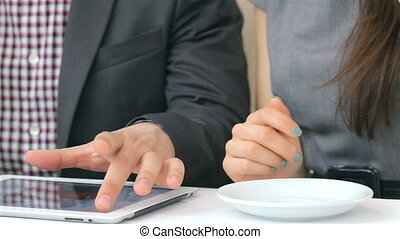 Close-up of hands show on the tablet, cups of coffee....