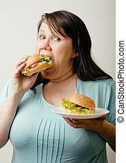 fat woman having choice between hamburger and salad
