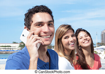 Mexican guy talking at phone with two girlfriends in the...
