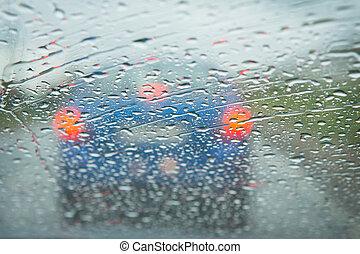 rain on a car windshield - rain on the city street through a...