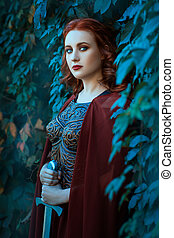 Girl with a sword standing in the bushes of grapes. The...