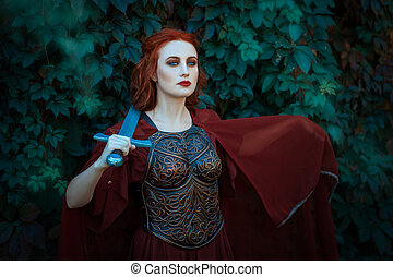 Red-haired girl warrior. In hands holds a sword on the chest...