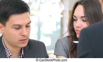 Close-up of face, young attractive couple consults about...