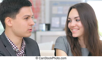 Attractive professional couple consults about their business...