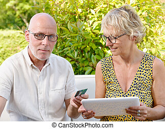 senior couple using tablet to make a purchase, - senior...