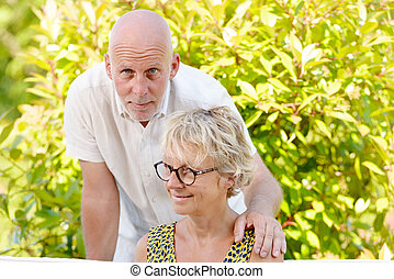 portrait of a senior couple sitting on a sofa outdoors