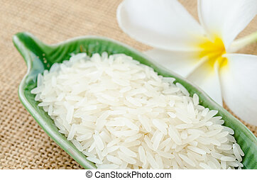 Raw white rice - Raw white rice in green cup with flower on...