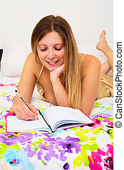 writing in diary - young woman in her bed writing in her...