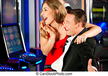Couple in Casino on a slot machine