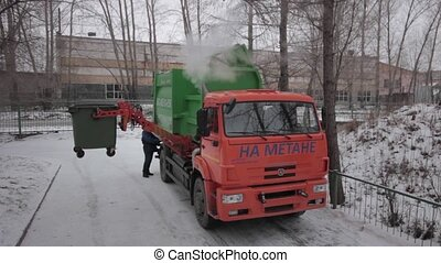 Garbage Trucks work - garbage truck loads trash into the...