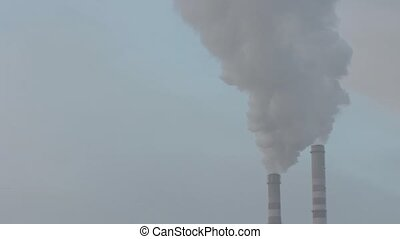 Air pollution by smoke coming out of two factory chimneys