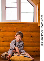 Little boy reading book sitting on the floor