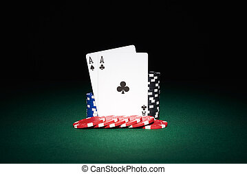 Poker chips on table with aces cards in casino with black...