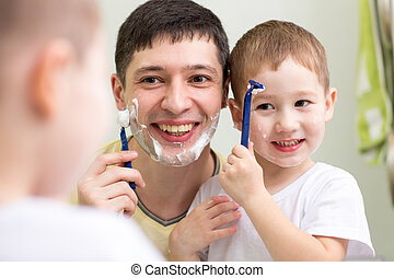 cute child boy and daddy shave looking at mirror in bathroom...