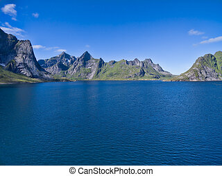 Fjord - Norwegian fjord surrounded by mountain peaks on...