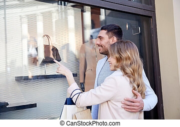 happy couple with shopping bags at shop window - sale,...