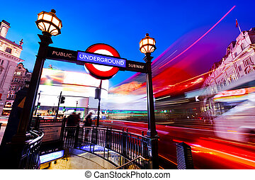 Underground sign, red bus in motion on Piccadilly Circus. London, UK at night