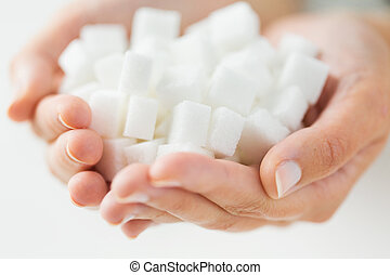 close up of white lump sugar in woman hands - food,...