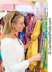 Young woman choosing scarf in the shop.