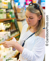 Young woman choosing cosmetic cream in beauty shop.