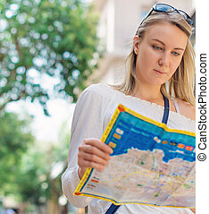 Woman with map in the street. Place for your text.