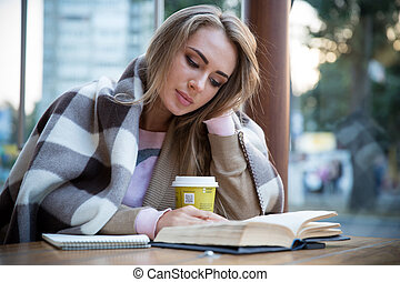 Girl reading book in cafe - Portrait of a charming girl...