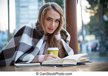 Portrait of a happy girl sitting with book in cafe and...