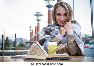 Student sitting with book and coffee in cafe - Portrait of a...
