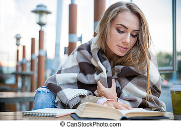 Woman reading book in cafe - Portrait of attractive young...