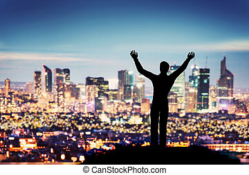Successful businessman with hands up facing city business...