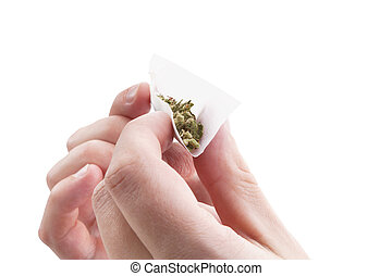 Preparing a cannabis joint. - Hands isolated on white...