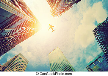 Airplane flying over modern business skyscrapers. Transport, travel.