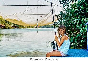 Little girl fishing on the river Bojana in Montenegro