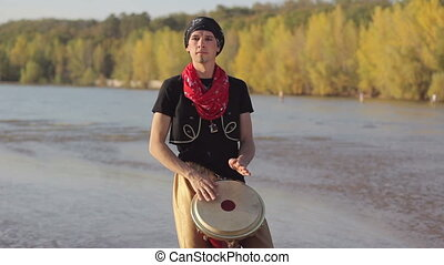 The man plays on a drum in ethnic dress on nature
