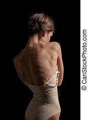 Beautiful woman, back view on dack background - A beautiful...