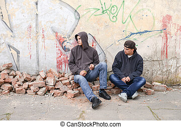 Two street hooligans or rappers sitting against a graffiti...