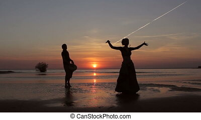 Silhouette girl dancing exotic dance with drummer -...