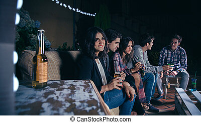 Woman holding beer and her friends talking in a party -...