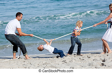 Merry family playing tug of war at the beach