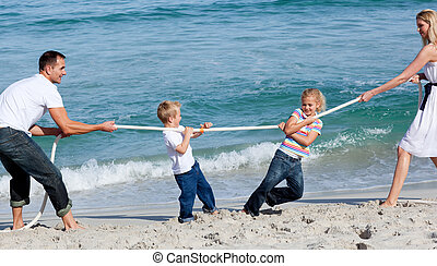Happy family playing tug of war at the beach