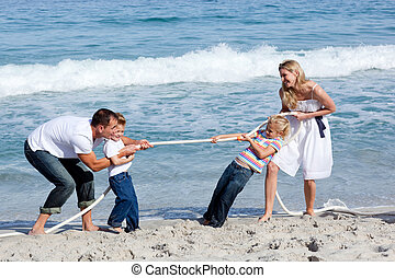Cheerful family playing tug of war at the beach