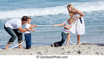 Lively family playing tug of war at the beach